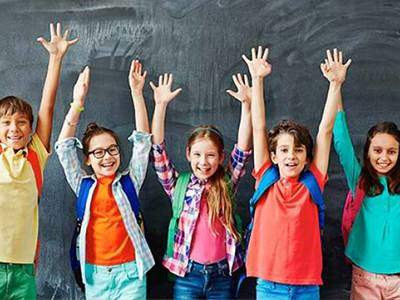 Excited children holding both hands in the air in front of a chalkboard.